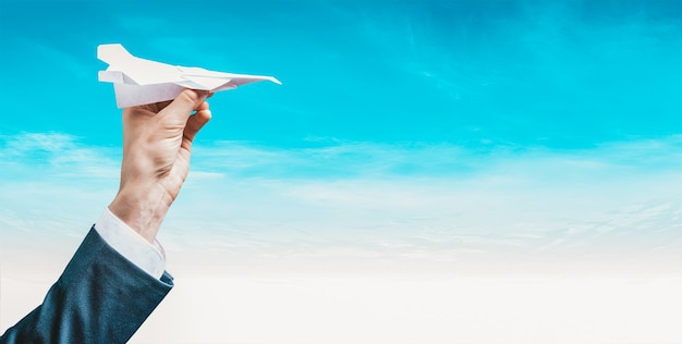 Image of a hand holding a paper airplane. tourism concept.