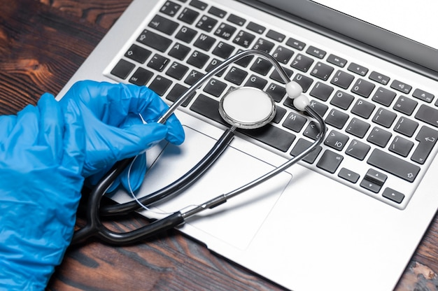 Image of hands in medical gloves. against the wall of a laptop and a stethoscope.