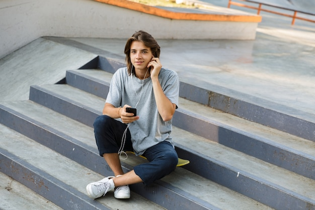 Image of handsome attractive young skater guy sit in the park listening music with earphones using phone.