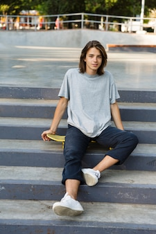 Image of handsome attractive young skater guy sit in the park posing