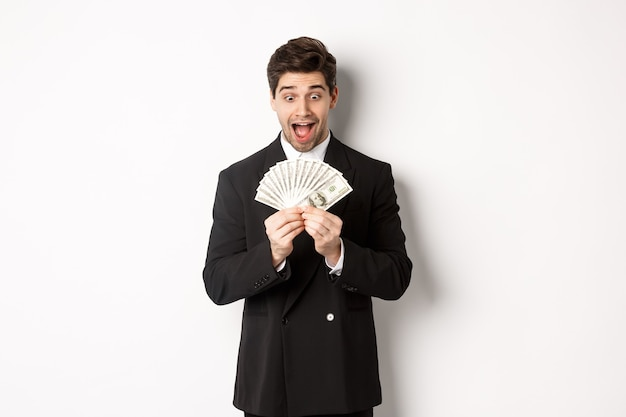 Image of handsome bearded guy in black suit, looking at money with excitement, standing over white background.
