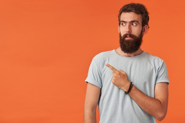 Image of handsome bearded young man with brown eyes in casual clothes white t-shirt is pointing away, looking aside emotion surprised or confused