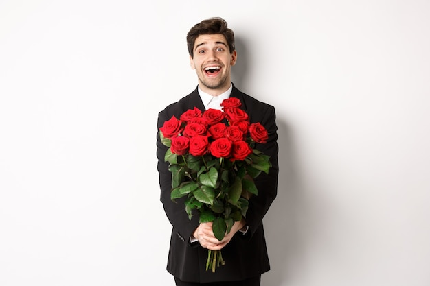 Image of handsome boyfriend in black suit, holding bouquet of red roses and smiling, being on a date, standing over white background.