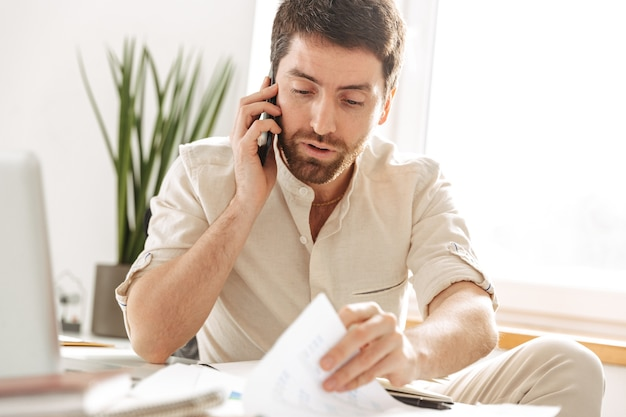 Image of handsome businessman 30s wearing white shirt talking on mobile phone, while sitting at table in modern office