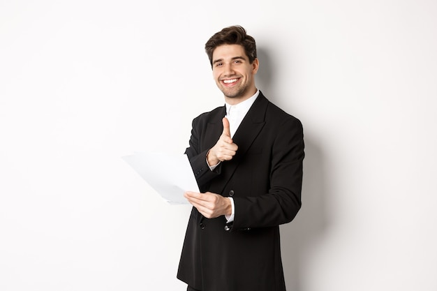 Image of handsome businessman in black suit, holding document and pointing finger at camera, praising good job, standing against white background