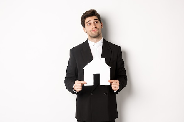 Image of handsome businessman in black suit, looking for home, holding house maket and gazing dreamy at upper right corner, standing against white background
