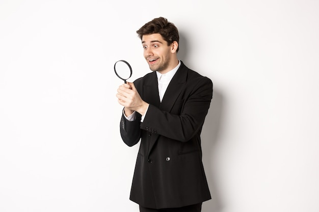 Image of handsome businessman in black suit, looking through magnifying glass, found something and smiling, standing over white background.