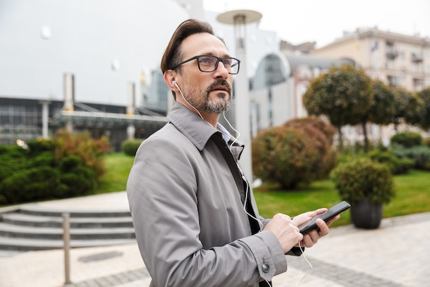 Image of handsome businessman in eyeglasses using cellphone and earphones while walking at city street