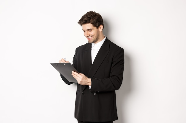 Immagine di un bell'uomo d'affari in tuta che firma documenti, guarda gli appunti e sorride, in piedi su sfondo bianco.