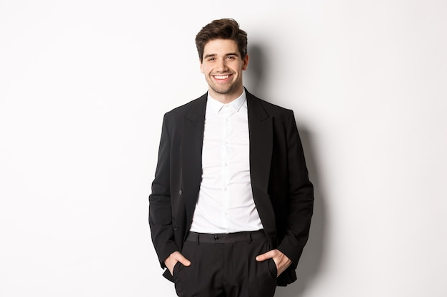 Image of handsome caucasian man in party suit, smiling pleased, attend formal event, standing over white background