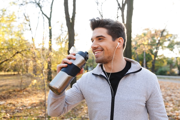 Image of a handsome emotional young sportsman outdoors in park listening music with earphones drinking water.