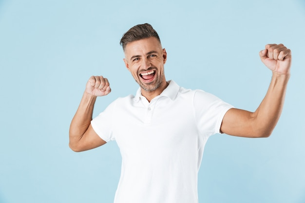 Image of a handsome excited emotional adult man posing over blue wall dancing.