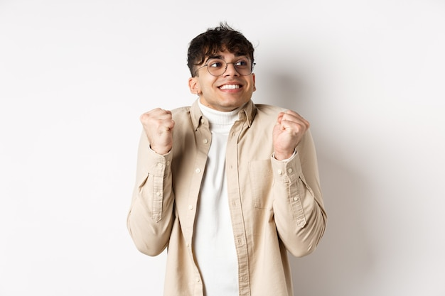 Image of handsome excited man feeling motivated and lucky, looking right and smiling, making fist pump gesture to celebrate victory, winning prize, standing on white wall.