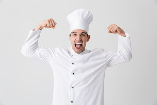 Image of handsome excited young man chef indoors isolated over white wall background showing biceps. Premium Photo