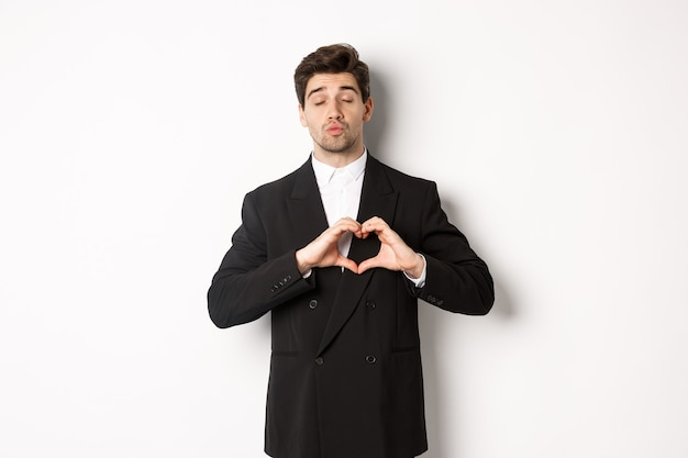 Image of handsome groom in black suit, showing heart sign, close eyes and pucker lips, waiting for kiss, standing against white background