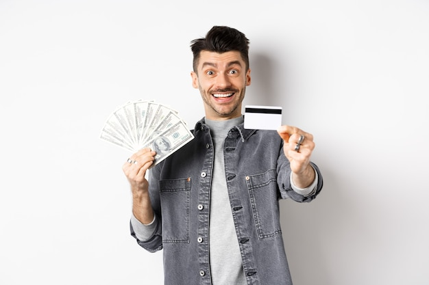 Image of handsome guy holding dollar bills but suggesting use plastic credit card, smiling friendly at camera, standing on white background.