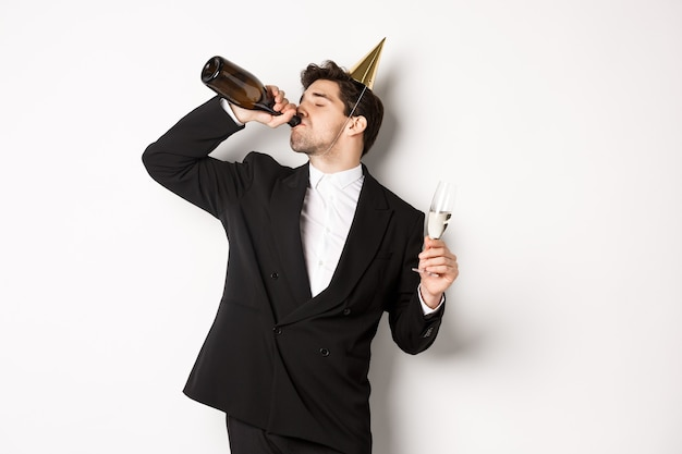 Image of handsome guy in trendy suit, drinking champagne from bottle and celebrating holiday, having a birthday party, getting drunk while standing over white background.