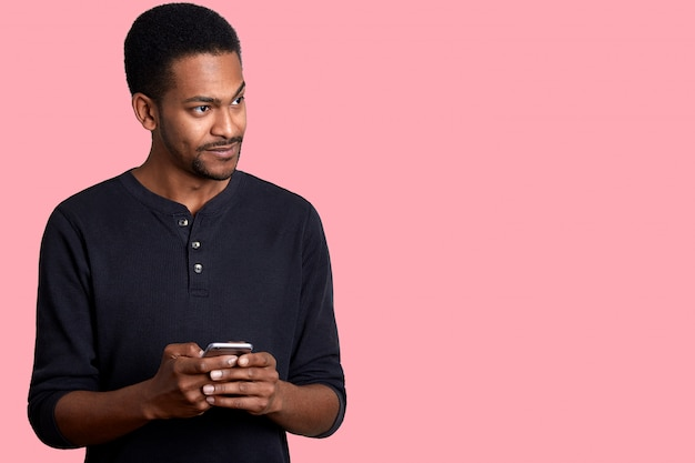 Image of handsome guy with dark skin, in black shirt, stands and holds phone in hand, looks aside with uncomprehending, hears unpleasent conversation near him while typing message