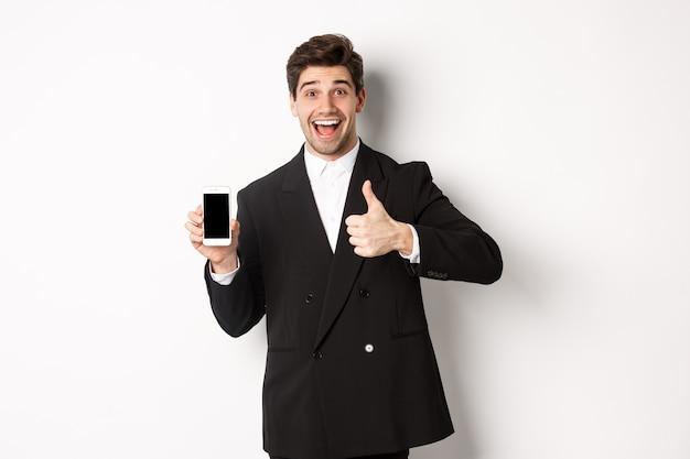 Immagine di un bell'imprenditore maschio in abito nero, che consiglia app o negozio online, che mostra il pollice in su e lo schermo dello smartphone, in piedi su sfondo bianco
