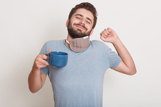 Image of handsome male has morning coffee, still sleeps, yawns, standing indoor isolated over white