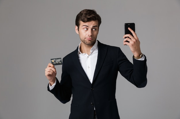 Image of handsome man 30s in business suit holding black mobile phone and credit card, isolated over gray wall