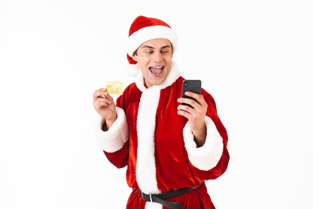 Image of handsome man 30s in santa claus costume holding smartphone and credit card
