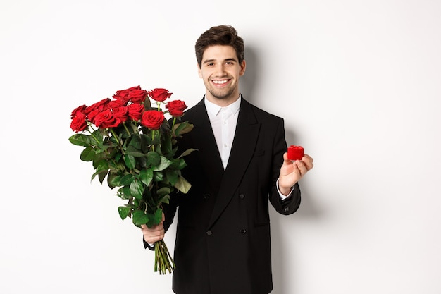 Image of handsome man in black suit, holding bouquet of red roses and a ring, making a proposal, smiling confident, standing against white background.