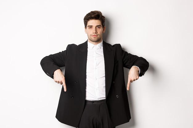 Image of handsome man dressed for formal party, wearing suit and pointing fingers down, showing advertisement or making announcement, standing over white background.
