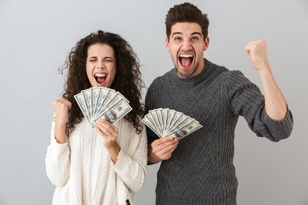 Image of handsome man and pretty woman holding fan of dollar money, isolated over gray wall
