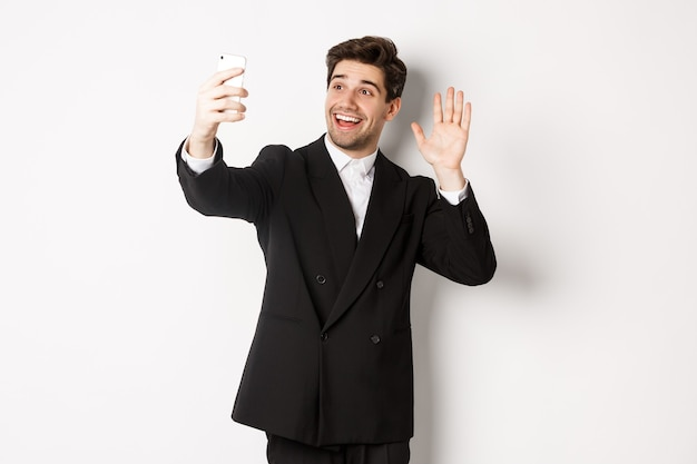 Image of handsome man in suit, having video call and waving hand at smartphone camera, recording video, greeting someone, standing against white background.