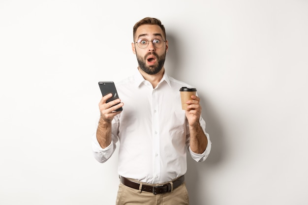 Image of handsome manage drinking coffee, reacting surprised to message on mobile phone, standing over white background.