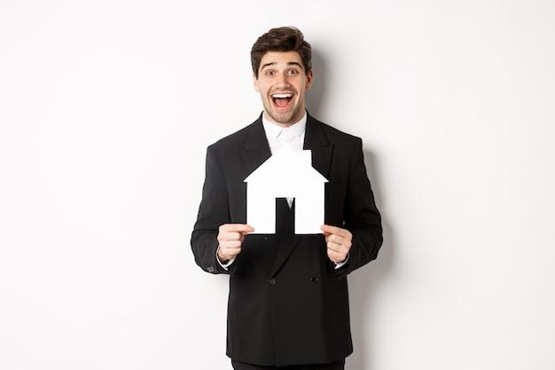 Immagine di un bell'agente immobiliare in abito nero che mostra il maket domestico e sembra stupito, vende case, in piedi su sfondo bianco