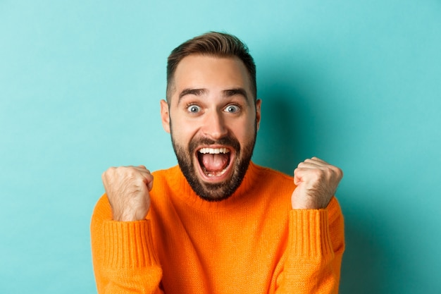 Image of handsome relieved man feeling satisfaction, rejoicing of winning or achievement, making fist pump and saying yes, standing over turquoise background.