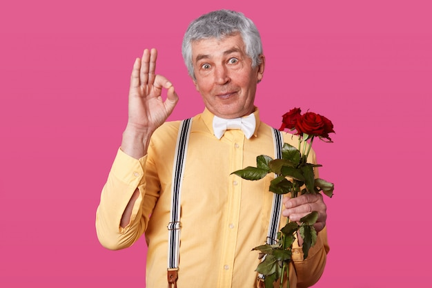 Image of handsome senior man showing okay sign, ready to go on dating, holds red flowers in hand, wears yellow shirt and bowtie, isolated on pink, posing in studio. body language concept.