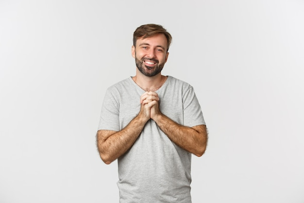 Image of handsome thankful man, holding hands together and expressing gratitude