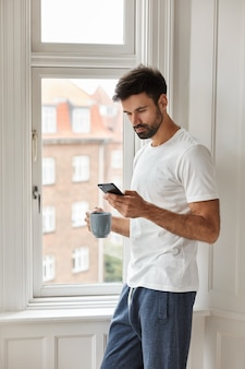 Image of handsome young caucasian man with thick bristle, dressed in casual t shirt, uses new cellular, holds cup with coffee, stands near window