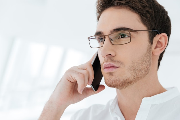 Image of handsome young man dressed in white shirt standing near big white window while talking by phone. look aside.