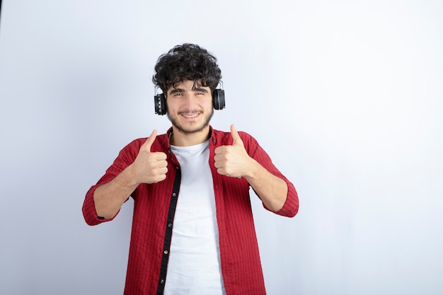 Image of handsome young man in headphones listening to song over white wall.