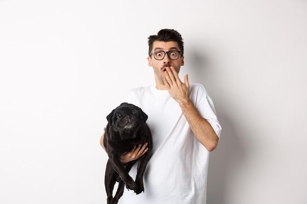 Immagine di un bel giovane che tiene in mano un cane carino e che boccheggia sorpreso. il proprietario dell'animale domestico fissa la telecamera scioccato, porta in braccio un carlino nero, sfondo bianco.