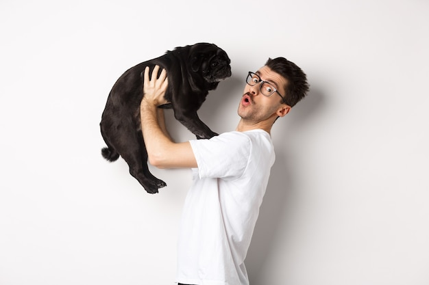 Image of handsome young man loving his pug. dog owner holding puppy and smiling happy at camera, standing over white background.