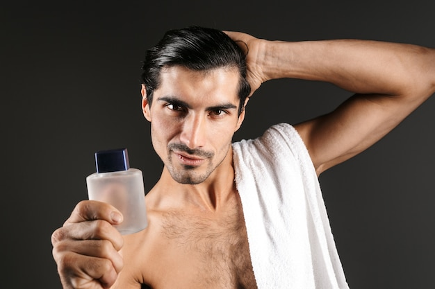 Image of handsome young man posing isolated holding toilet water.