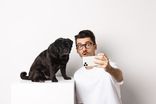 Image of handsome young man taking selfie with cute black dog on smartphone, posing with pug over white