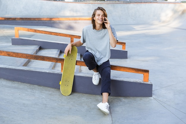 Image of handsome young skater guy sit in the park with skateboard talking by mobile phone.