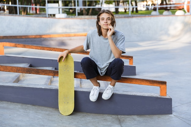 Image of handsome young skater guy sit in the park with skateboard.
