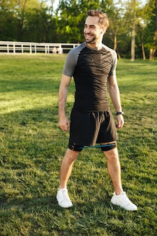Image of a handsome young strong sports man posing outdoors at the nature park location make exercises with fitness equipment.