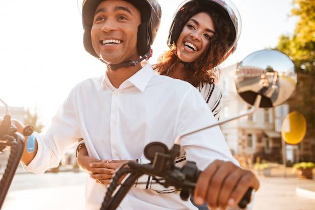 Image of happy african couple rides on modern motorbike on the street