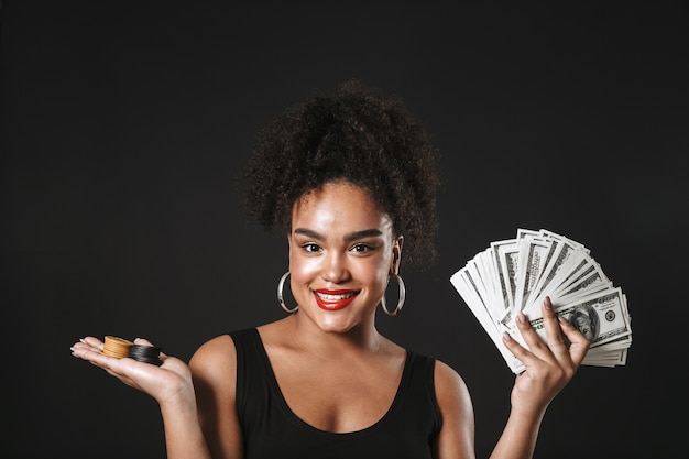 Image of a happy african woman posing isolated over black wall holding money and chips.