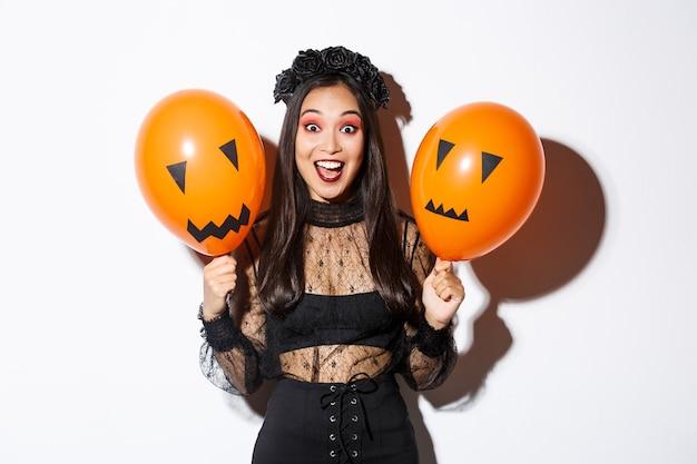 Immagine di felice donna asiatica in costume da strega che celebra halloween, tenendo palloncini con facce spaventose, in piedi su sfondo bianco.