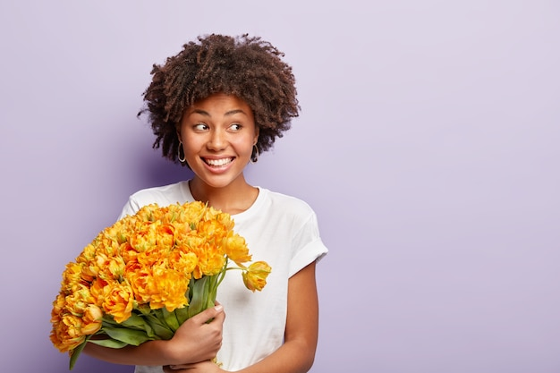 Image of happy birthday woman, celebrates special day, gets big bouquet of orange flowers, wears casual t shirt, focused aside, has smile on face, looks aside, meets guests, wears casual t shirt