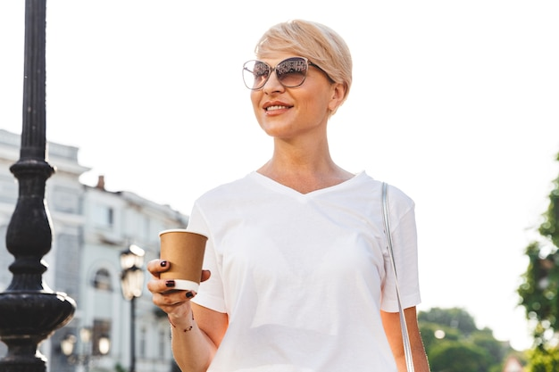 Image of happy blond woman wearing white t-shirt and sunglasses walking through city street in summer, and holding takeaway coffee